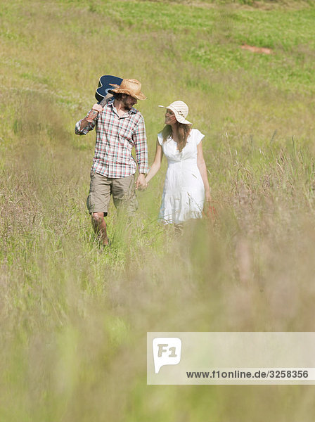 couple walking through long grass