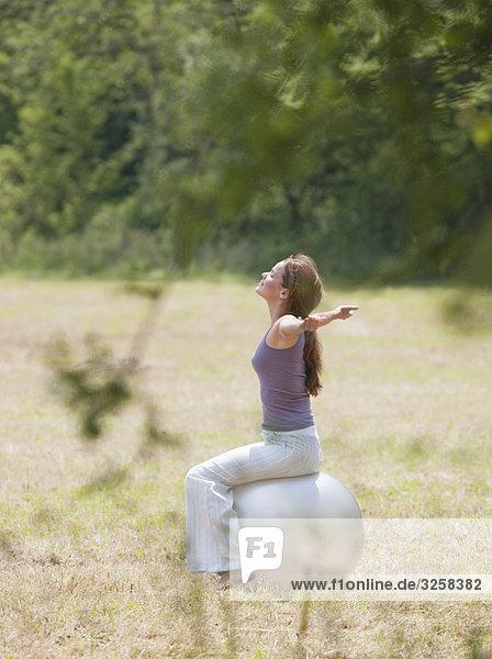 woman sat on yoga ball stretching