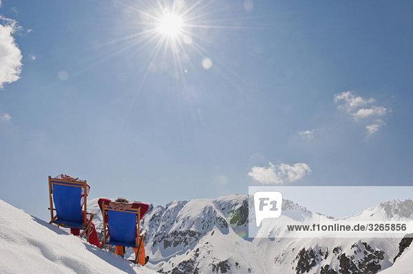 Österreich  Salzburger Land  Paar im Liegestuhl  Rückansicht
