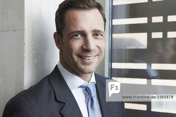 Deutschland  Köln  Geschäftsmann am Fenster  lächelnd  Portrait  Nahaufnahme