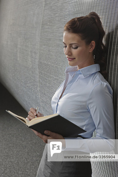 Businesswoman in office holding personal organizer  side view  portrait