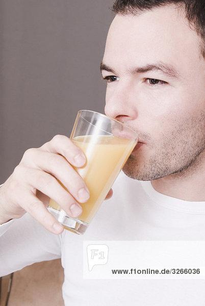 Mann trinkt ein Glas frischen Orangensaft  Portrait  Nahaufnahme