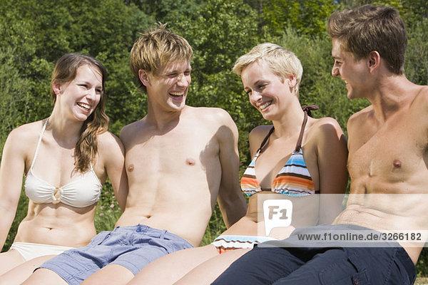 Deutschland  Bayern  Jugendliche in Badebekleidung  Seite an Seite  lächelnd  Portrait  Nahaufnahme