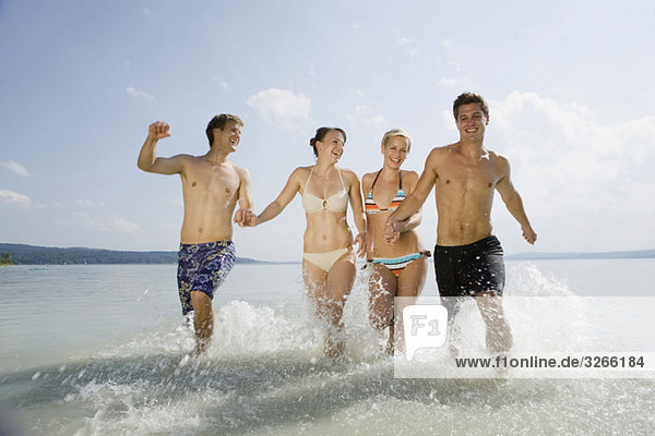 Germany  Bavaria  Ammersee  Young people running into lake