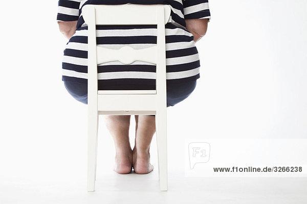 Übergewichtige Frau auf Stuhl  Rückansicht