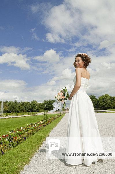 Deutschland  Bayern  Braut im Park mit Blumenstrauß  lächelnd  Portrait