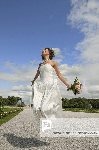 Deutschland  Bayern  Braut im Park Springen in der Luft  lächelnd  Portrait