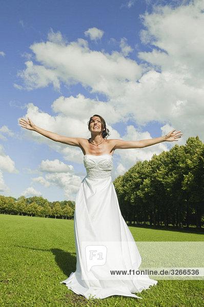 Deutschland  Bayern  Braut im Park mit ausgestreckten Armen  lächelnd  Portrait