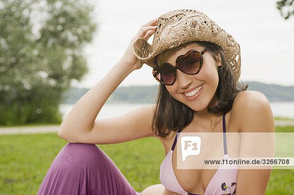 Starnberger See  Junge Frau sitzt im Park mit Sonnenbrille und Hut  lächelnd  Portrait  Nahaufnahme