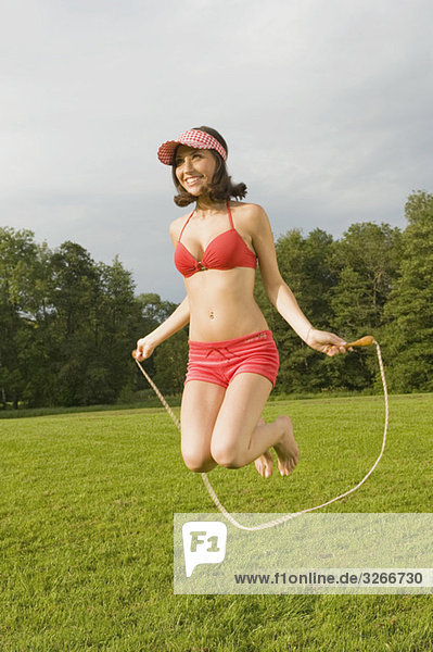Starnberger See  Young woman jumping rope in meadow  smiling  portrait
