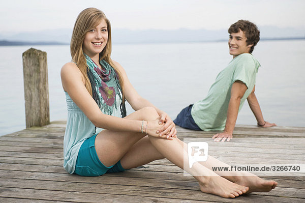 Germany  Bavaria  Starnberger See  Young couple sitting on jetty