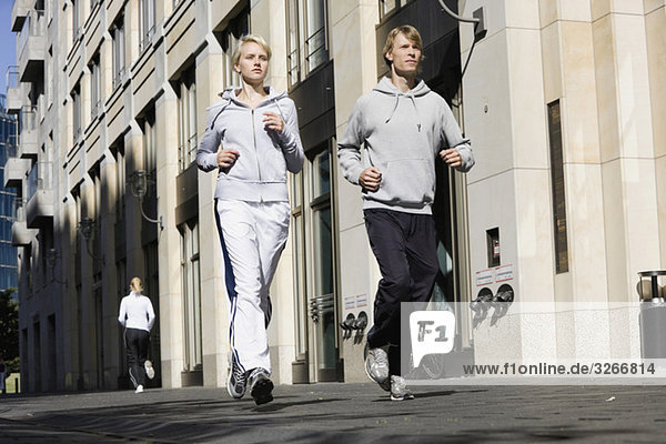 Germany  Berlin  Young couple jogging together