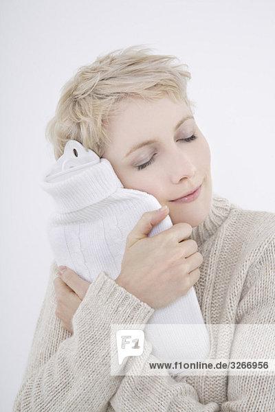 Frau hält Wärmflasche  Augen geschlossen  Portrait