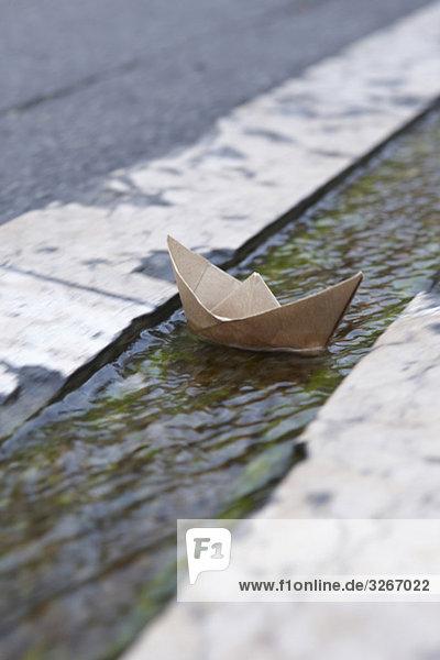 France  Paper Boat floating in gutter France, Paper Boat floating in gutter