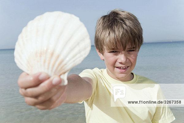 Spanien  Mallorca  Junge (8-9) hält Muschel am Strand  Portrait