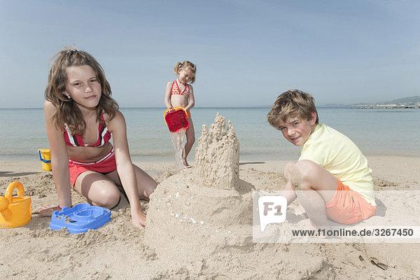 Spain  Mallorca  Children building sandcastle on beach
