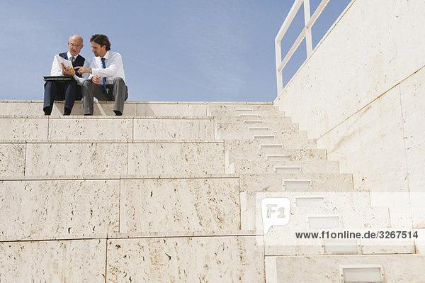 Spanien  Mallorca  Geschäftsleute sitzen auf einer Treppe und halten Dokumente.
