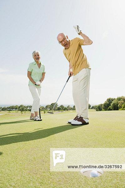 Spanien  Mallorca  Seniorenpaar auf dem Golfplatz  Männerjubel