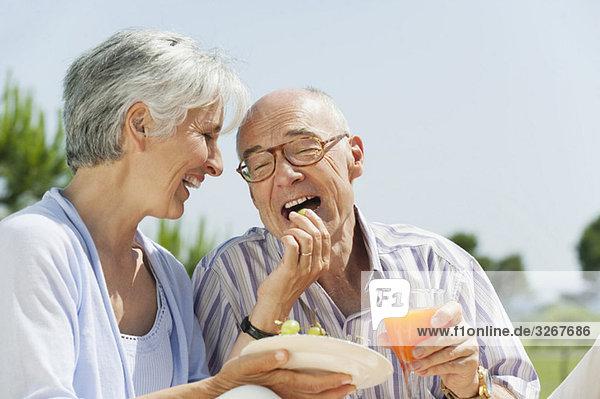Spanien  Mallorca  Seniorin beim Traubenfüttern  lachend  Portrait Spanien, Mallorca, Seniorin beim Traubenfüttern, lachend, Portrait
