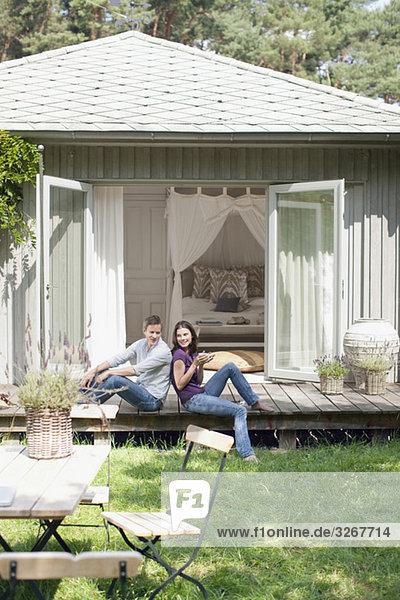 Paar sitzend Rücken an Rücken auf Terrasse  Frau hält Tasse