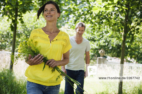 Couple in garden  woman holding bunch of flowers