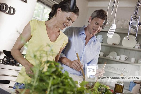 Germany  Hamburg  Couple preparing food in kitchen