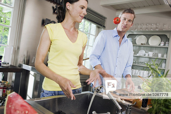 Germany  Hamburg  Couple in kitchen  fooling about with tomato