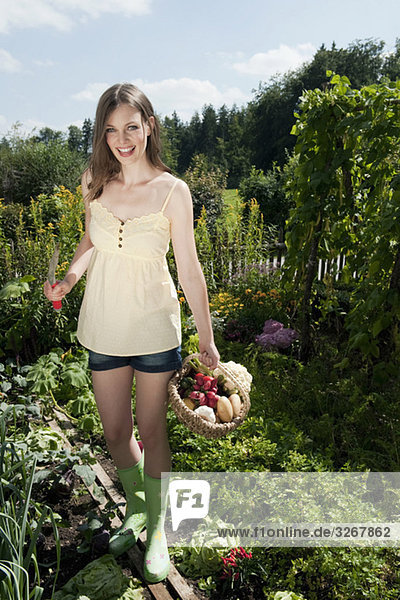Young woman holding basket of vegetables in garden  smiling  portrait
