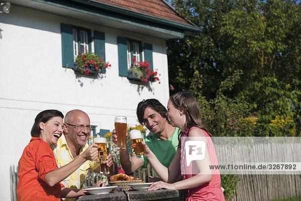 Deutschland  Bayern  Vier Personen trinken Bier im Garten  Spaß haben  Portrait