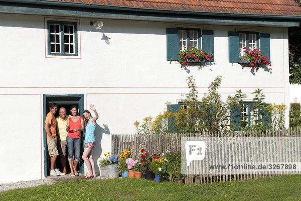Deutschland  Bayern  Vier Personen winken vor der Haustür  Portrait