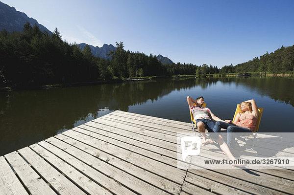 Italien,  Südtirol,  Paar Sonnenbaden in Stühlen am Steg