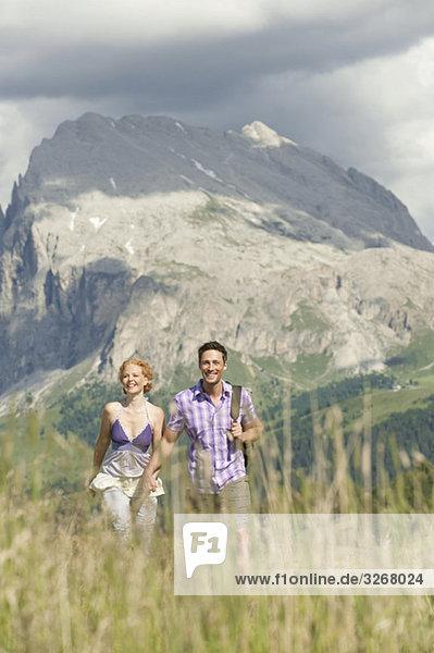 Italien  Seiseralm  Paar geht Hand in Hand auf Wiese