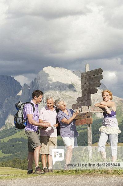 Italien  Seiseralm  Männer und Frauen stehen am Wegweiser  lächelnd