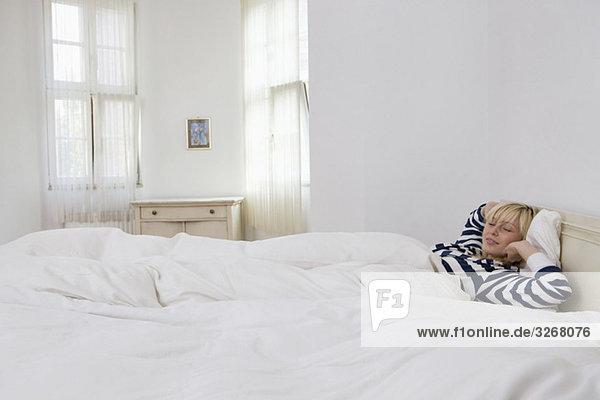 Junge Frau  die im Bett schläft.