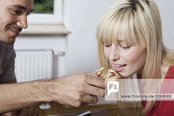 Junger Mann füttert Frau mit Brötchen  Porträt