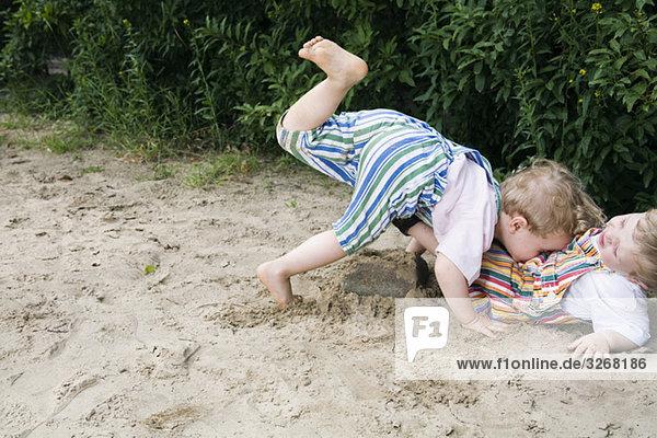 Zwei Jungen (1-3)  die zusammen im Sand spielen