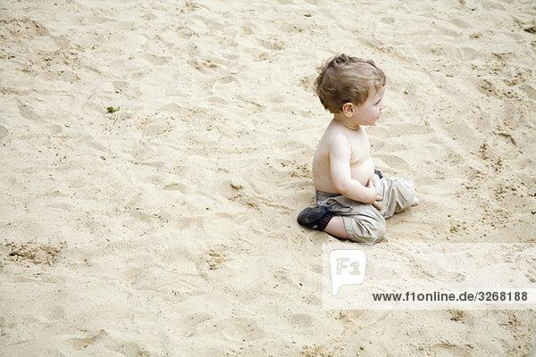 Kleiner Junge (18-23 Monate) im Sand sitzend Kleiner Junge (18-23 Monate) im Sand sitzend