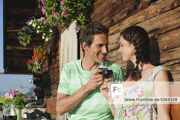 Italien  Südtirol  Paar vor dem Blockhaus mit Weingläsern  lächelnd  Portrait