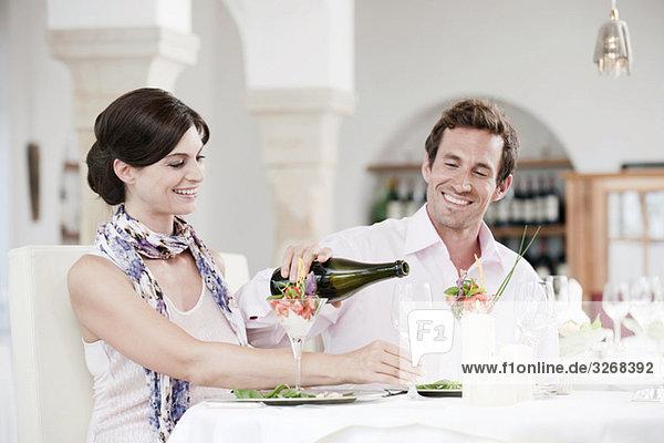 Paar im Restaurant  Mann gießt Wein ins Glas  lächelnd  Portrait