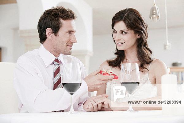 Paar am Tisch im Restaurant sitzend  Mann mit Geschenkpaket