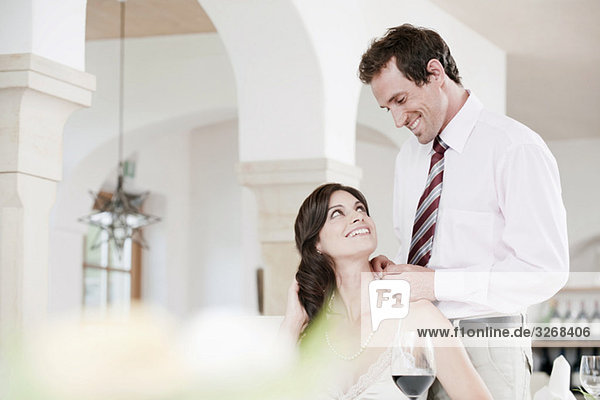 Couple in restaurant  man placing necklace on woman