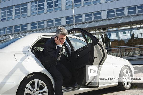 Deutschland  Hamburg  Geschäftsmann mit Handy  Auto verlassen  Seitenansicht