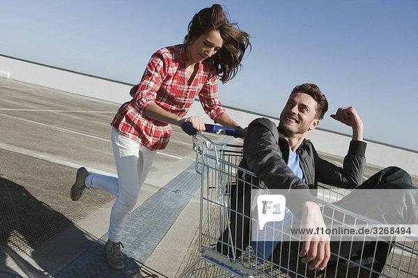 Junge Frau schiebt jungen Mann in den Einkaufswagen.