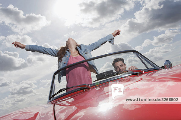 Young couple in cabriolet  woman with arms outstretched