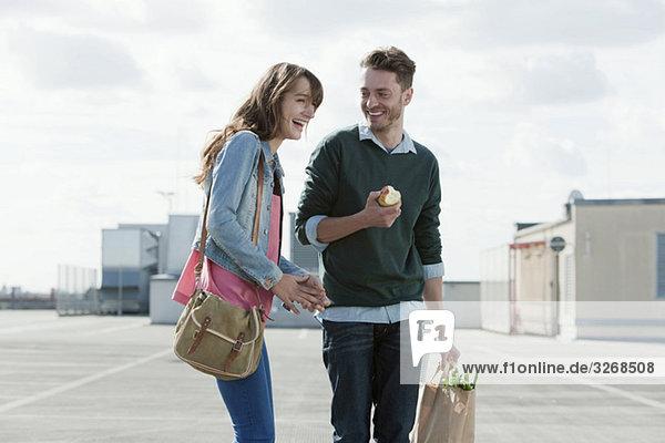 Junges Paar auf Parkebene stehend lachend  Mann mit Apfel  Porträt