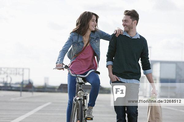 Deutschland  Berlin  Junges Paar mit Fahrrad und Papiertüte