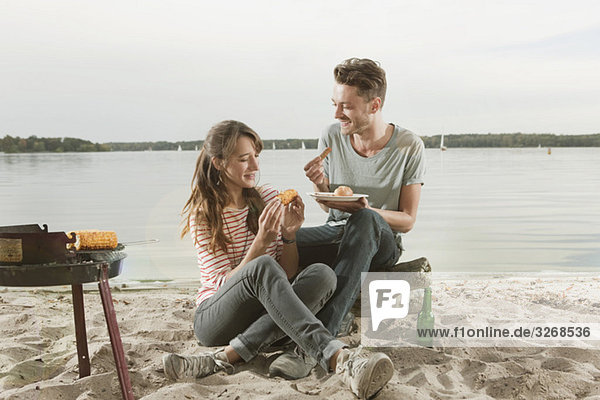 Germany  Berlin  Lake Wannsee  Young couple having a barbecue