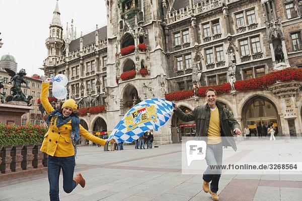 Deutschland  Bayern  München  Paar mit Luftballons und bayrischer Flagge  lachend  Portrait