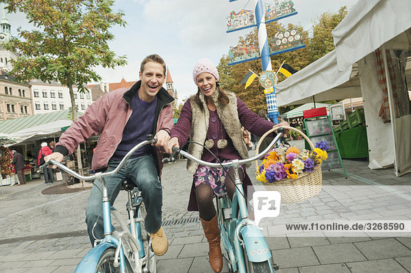 Germany  Bavaria  Munich  Viktualienmarkt  Couple with bicycles  laughing  portrait