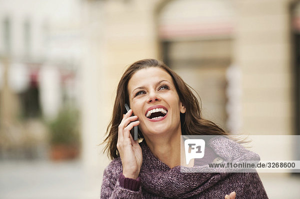 Woman using mobile phone  laughing  portrait